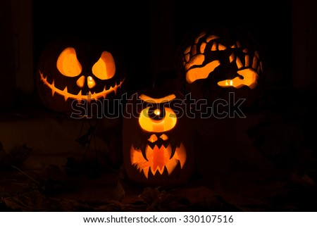 Photo composition from three pumpkins for Halloween. Jack, a Cyclops and hands of pumpkin against autumn leaves and candles - stock photo