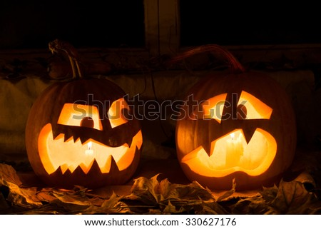 Photo composition from two pumpkins on Halloween. Embittered and frightened pumpkins stand against an old window, leaves and candles. - stock photo