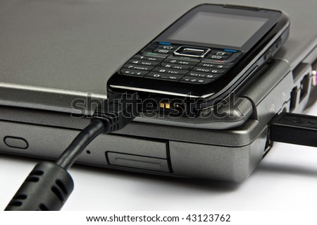 photo concept phone connected to laptop via usb cable - stock photo