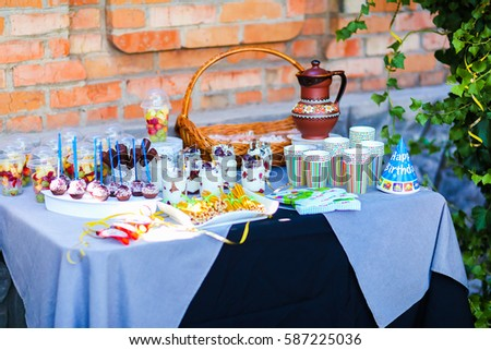 Photo decorated table for children's parties, birthday against backdrop of orange brick wall. In photo depicts variety treats, delicious food, clear jars with cottage cheese soufflé with layer of