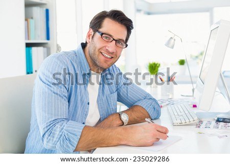 Photo editor writing on a paper while looking at camera on office - stock photo