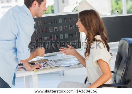 Photo editors discussing together while working on computer - stock photo