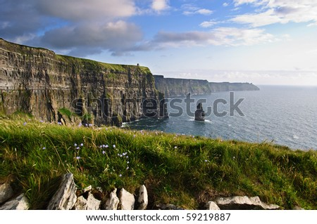 photo famous cliffs of moher sunset, west coast of ireland. beautiful walk for people along hiking trial on the atlantic way route by the ocean beach.