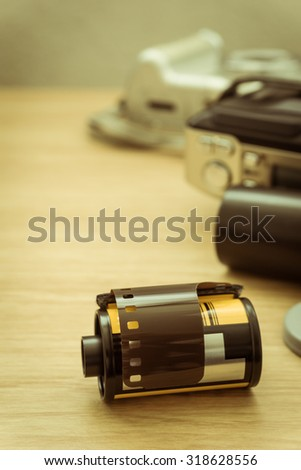 photo film in cartridge and film camera on wooden table.
