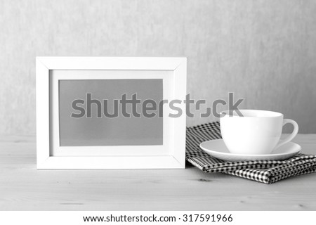 Photo frame and coffee cup on table cloth on wooden table - vintage effect style picture - stock photo