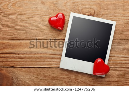 Photo frame and small red hearts on old wood background, path inside - stock photo