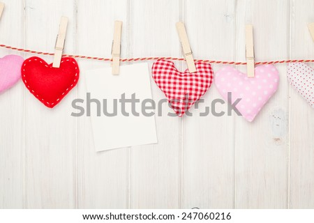 Photo frame and valentines day toy hearts over white wooden background - stock photo