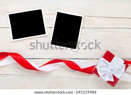 Photo frame cards and gift box with ribbon over wooden table background - stock photo