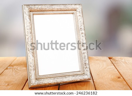 Photo frame on wooden table on bright background - stock photo