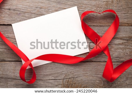 Photo frame or gift card with valentines heart shaped ribbon over wooden table background - stock photo