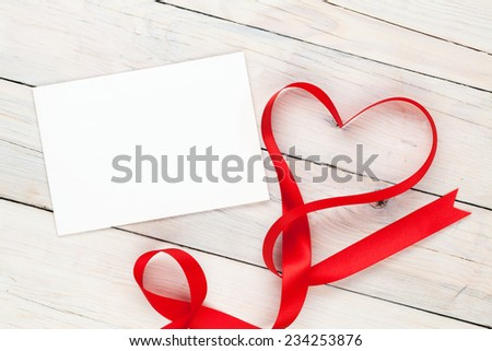 Photo frame or greeting card with valentines heart shaped ribbon over wooden table background - stock photo