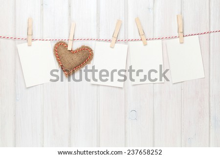 Photo frames and valentines toy heart over wooden background - stock photo