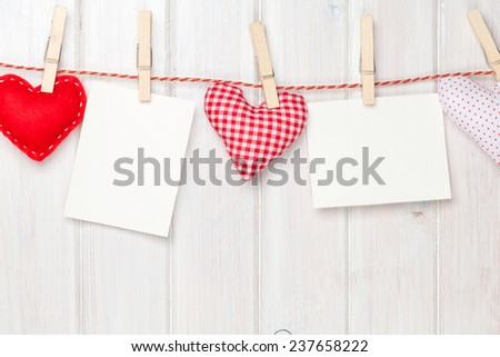 Photo frames and valentines toy hearts over wooden background - stock photo
