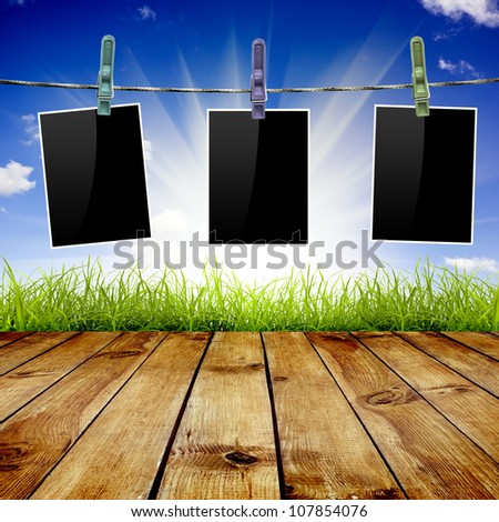 Photo frames pictures on blue sky, grass and wood floor background - stock photo