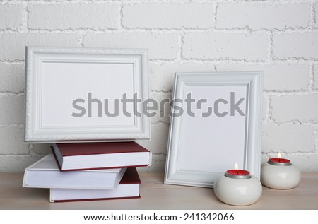 Photo frames with candles and books on wooden surface, on brick wall background - stock photo