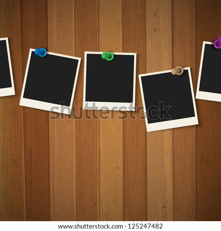 Photo frames with colored pushpins on wooden background. Raster version - stock photo