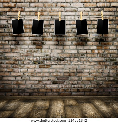 Photo frames with pins on rope over old aged brick wall and wood floor background - stock photo