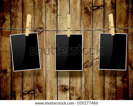 Photo frames with pins on rope over old aged wood background - stock photo