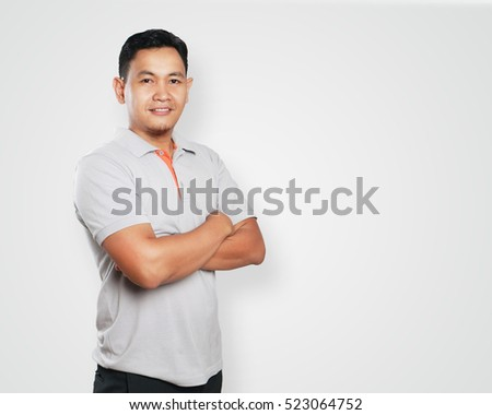 Photo image portrait of a cute handsome young Asian man smiling confidently with his arms crossed in front of his chest