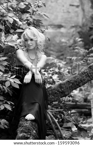 Photo in black and white. A gracious and delicate blonde woman in long black dress sitting pensively on a tree.