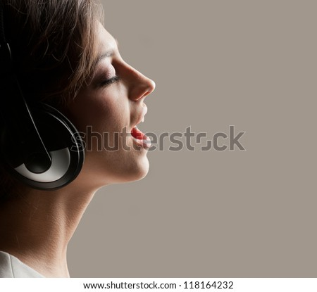 Photo in profile expressive girl in headphones singing emotionally - stock photo
