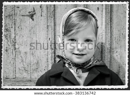 Photo in retro style. Cute little girl in a kerchief. Selective focus. - stock photo
