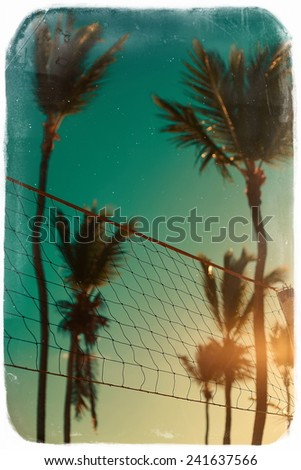 Photo in retro style with volleyball net on beach and palms behind blue summer sky - stock photo