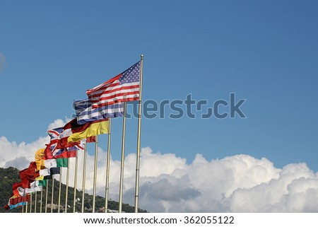 Photo long shot of row of different national flags flutter in wind on tall flagstaffs green mountains fluffy white clouds on blue sky background, horizontal picture  - stock photo