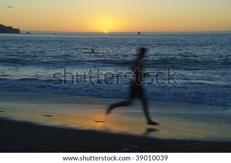 photo man running on the beach and sunset