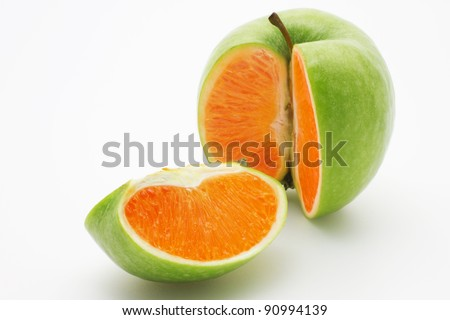 Photo manipulation:  green apple with orange content - stock photo