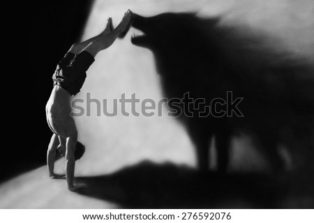 Photo-manipulation - handstand in studio with wolf shadow - stock photo