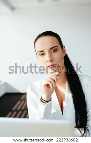 Photo of a attractive female white-collar worker sitting at the laptop