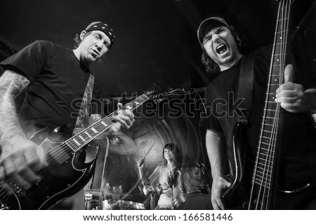 Photo of a band playing on stage. Male guitarist, male bassist and female drummer. Shot with strobes and slow shutter speed to create lighting atmosphere and blur effects. Slight motion blur visible. - stock photo