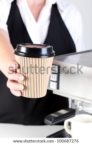 Photo of a Barista handing you a coffee in a disposable paper takeaway cup. - stock photo