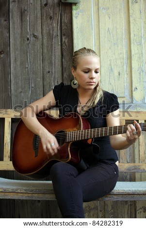 Photo of a beautiful blond female playing her acoustic guitar on an old wooden bench.