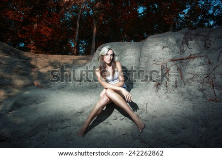Photo of a beautiful blonde, sexy appearance that posing in denim shorts and white T-shirt in the canyon sandy - stock photo