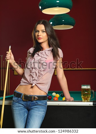 Photo of a beautiful brunette holding a pool cue and leaning against a pool table. - stock photo