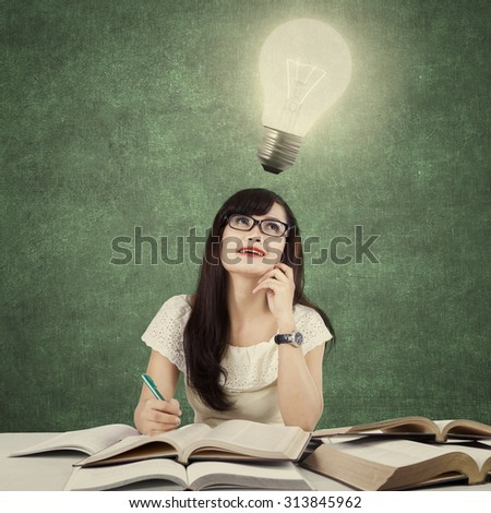 Photo of a beautiful female student sitting in the class while doing school task and get idea, looking at bright light bulb - stock photo