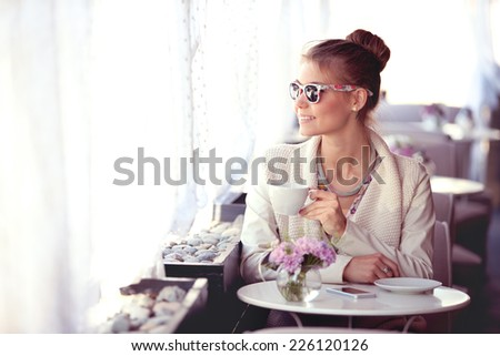 Photo of a beautiful happy young woman with smartphone and sunglasses, drinking hot tea or coffee on a cafe patio and looking out the window. - stock photo