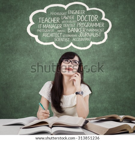 Photo of a beautiful high school student studying in the classroom while imagining her dream profession - stock photo