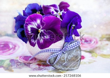 Photo of a beautiful purple pansy flowers and  wooden heart.  - stock photo