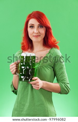 Photo of a beautiful redhead holding a huge mug of green beer on St. Patricks Day. - stock photo