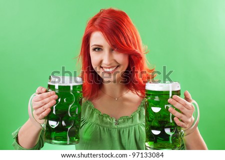 Photo of a beautiful redhead holding two huge mugs of green beer for St. Patricks Day celebrations. - stock photo