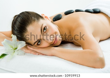 Photo of a beautiful smiling woman lying with spa stones on her back and looking at camera with white lily near by - stock photo