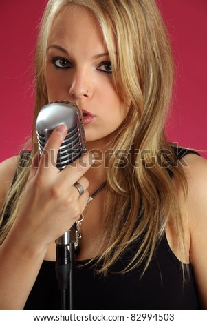 Photo of a beautiful young blond singing into a vintage microphone.