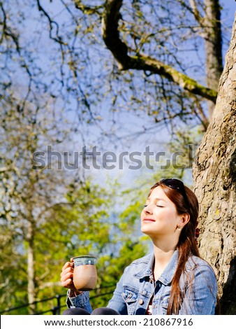 Photo of a beautiful young woman drinking coffee or tea while sitting outdoors enjoying the warmth of the sun on her face. - stock photo