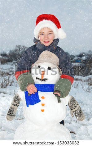 Photo of a boy aged 10-11 years in the hat of Santa Claus hugging a snowman. Snowfall. - stock photo