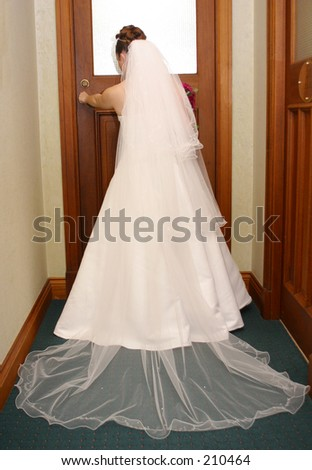 Photo of a bride opening a door, showing the back of her dress and veil.