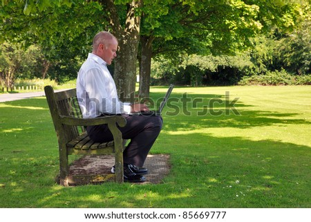 Photo of a businessman in smart casual clothing sat on a park bench working on his laptop computer. - stock photo