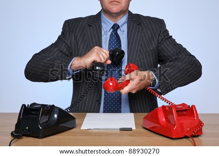 Photo of a businessman sat at a desk with two traditional telephones, one red and one black. Conference call concept. - stock photo